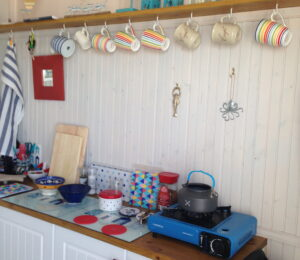Photo of the inside of a Bonningstedt Beach Huts, photo shows a gas burning with kettle. mugs and other sundries.