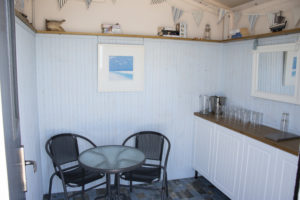 Photo of the example internal Bonningstedt Beach Hut set up, shows a table and chairs with a worktop.