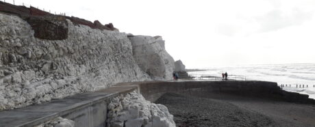 A photograph of Splash Point, a concrete path at the foot of cliff leading to a short curved pier out to sea
