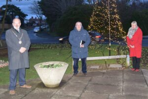 The Mayor, his Champlain and Deputy Mayor standing in front of the Christmas tree of lights at Seaford war memorial