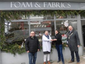 The winners of the best dressed window competition standing outside their shop, Foam and Fabrics being presented their trophy