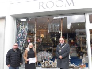 Runner up of the best dressed window competition standing outside their shop, Room being presented their prize