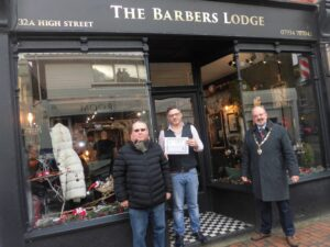 Runner up of the best dressed window competition standing outside their shop, The Barbers Lodge being presented their prize