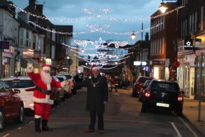 The Mayor and Sants standing in Seaford town centre pushing a button for the Christmas lights to come on