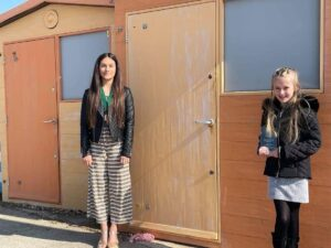 Young Mayor of Seaford and Young Mayor's awardee standing in front of beach huts on Seaford Beach holding the award