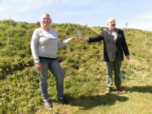 The Mayor of Seaford and Clare Sumnsers from Plastic Free Seaford standing on grass holding the award