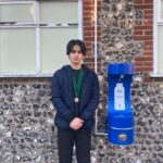 Young Mayor standing by water refill station attached to flint wall