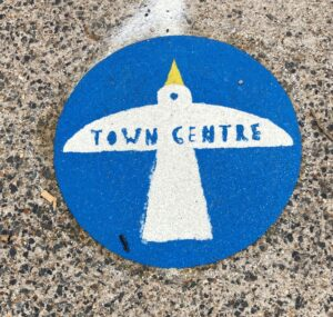 Gateway marker - a white seagull printed on a bright blue circle, bearing the words town centre