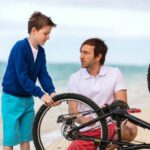 A man and boy repairing a bike on the seafront